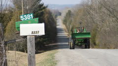 Tractor driving up steep hill on old country road by two mailboxes. 1080p 24. Stock Footage