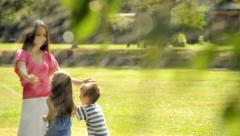 Kids are playing in a park with sprinklers. Stock Footage