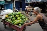 Stock Photo of senior balinese man pushing trolley with vegetables