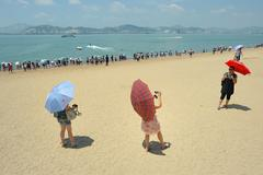 Chinese with umbrellas on the beach - stock photo