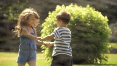 Kids are playing in a park with sprinklers. - stock footage