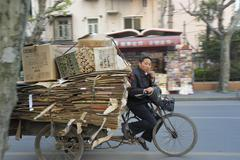 man riding tricycle with recycling paper in Shanghai - stock photo