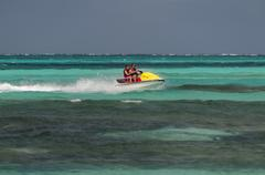 father and daughter riding a jet ski. - stock photo