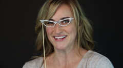 A cute Feminine Holds puppet eyeglass and exposes her pretty smile Stock Footage