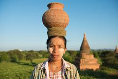 portrait of asian traditional farmer carrying pot on head - stock photo