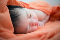 Newborn asian baby girl on bed Stock Photos