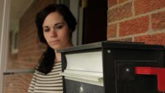 Woman getting mail from mailbox on porch jib Stock Footage