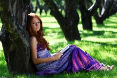 Stock Photo of young woman in summer, green park reading book