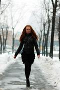 Young woman walking down snow covered street Stock Photos