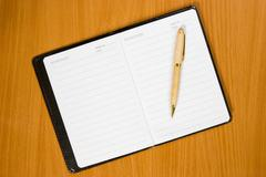 Stock Photo of notebook and pen on the  wooden table
