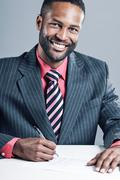 African american businessman signing a contract Stock Photos
