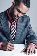 african american businessman signing a contract - stock photo