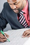 young african american businessman reading classifieds for a job - stock photo