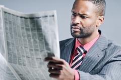 young african american businessman reading newspaper - stock photo