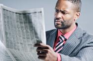 Stock Photo of young african american businessman reading newspaper