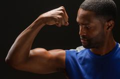 young african american man flexing biceps - stock photo
