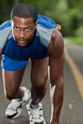 african american athlete running on a wooded path - stock photo