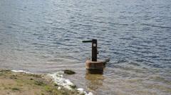 Sunken wooden row boat wave lake shore ripple water Stock Footage