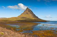 Stock Photo of western icelandic kirkjufell mountain landscape under a blue summer sky.