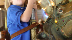 A cute little child plays the merry-go-round Stock Footage