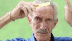 Elderly hispanic man looking and smiling at camera, brushing hair Stock Footage