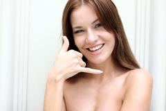 Beautiful woman making a call me gesture Stock Photos