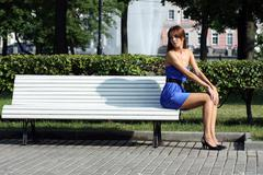 beautiful young woman sitting on a park bench - stock photo