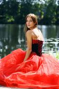Stock Photo of smiling woman in a red dress sitting near river