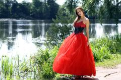 young woman in a red gothic dress - stock photo
