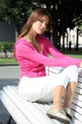 Beautiful young woman sitting on a park bench Stock Photos