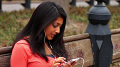 Woman Listening to Music in Park on Smartphone Stock Footage