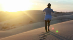 Sexy brunette girl in white dress posing on sand dune Stock Footage