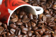 Coffee beans pouring out of a coffee cup Stock Photos