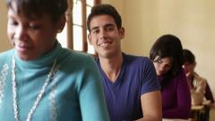Portrait of happy hispanic man smiling during test at university - stock footage
