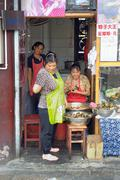 Women preparing food in street Stock Photos