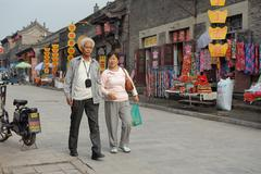 two seniors  walking in the street in pingyao - stock photo