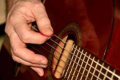 Playing on a guitar Stock Photos