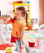 child with paint and brush in playroom. - stock photo