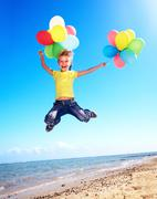 child playing with balloons at the beach - stock photo