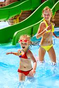 children on water slide at aquapark. - stock photo
