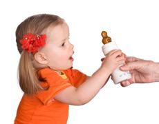 child take  small bottle with milk and dummy - stock photo