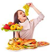 Woman choosing between fruit and hamburger. Stock Photos