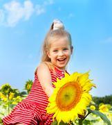 Stock Photo of kid holding sunflower outdoor.