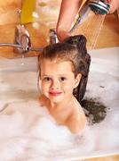 Kid washing hair by shampoo . Stock Photos