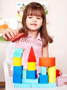 Stock Photo of child with wood block in play room.