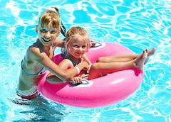 children sitting on inflatable ring. - stock photo