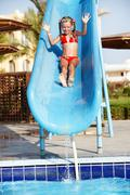 Girl sliding down water slide. Stock Photos
