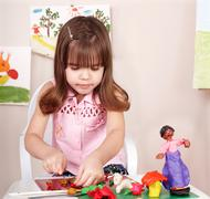 child playing with plasticine in school. - stock photo