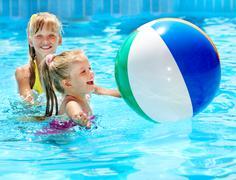 two girls swimming in pool - stock photo