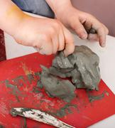 Stock Photo of child moulding from clay in play room.